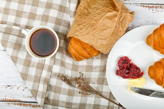 バターとジャムのクラサン。朝の初め。一杯のコーヒー。新鮮なフランスのクロワッサン。コーヒーカップと木製の背景に焼きたてのクロワッサン。上からの眺め。