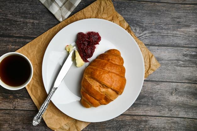 バターとジャムのクラサン。朝の初め。一杯のコーヒー。新鮮なフランスのクロワッサン。コーヒーカップと木製の焼きたてのクロワッサン。 。