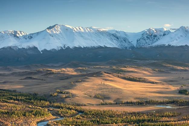 Курайская степь и заснеженный горный хребет осенью, сибирь. алтай. россия