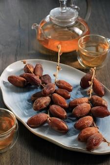茶色の木製テーブルの上の楕円形のプレートにクルマ乾燥ナツメヤシフルーツ、茶色のテーブルの背景にお茶を添えて
