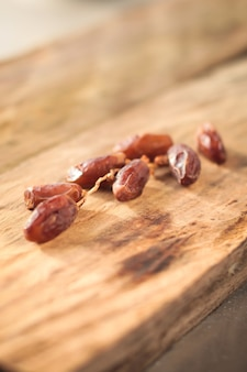 Kurma or dried dates, rosary wooden background.