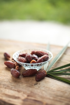 Kurma or dried dates, rosary on wooden background.