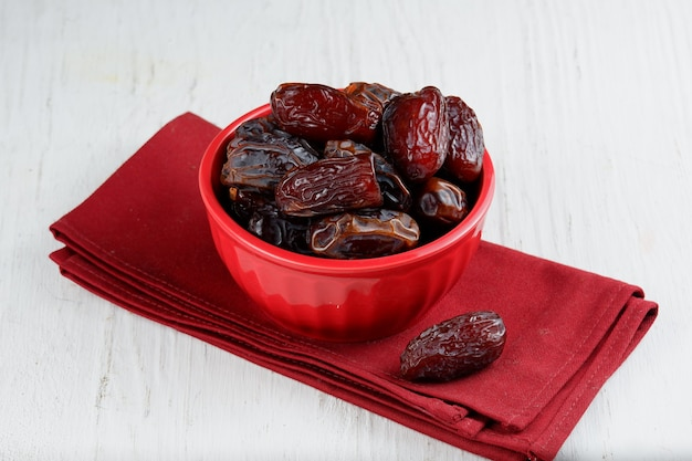흰색 배경에 있는 그릇에 쿠르마 또는 달콤한 말린 야자 과일
