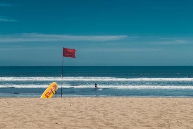 クタビーチ、バリ島、インドネシア。サーフレスキューポイント。黄色のレスキューサーフボードと赤い旗。