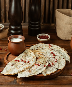 Kutab served with pomegranate seeds and yogurt in pottery jar
