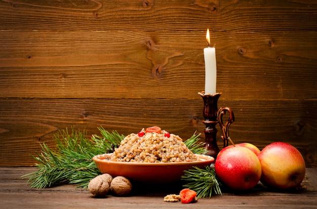 クリスマスイブkutiaのスラブ人の伝統的なクリスマスの御treat走。モミ枝、リンゴ、木製の背景にキャンドル