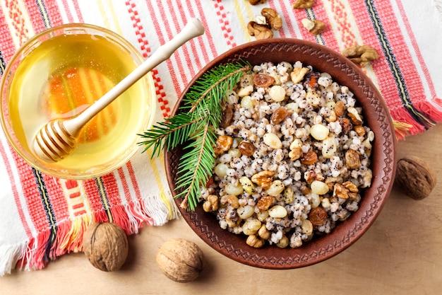 Кутья - это церемониальное зерновое блюдо со сладким соусом, которое традиционно подают восточно-православные христиане во время праздничного сезона рождества и иордании, а также как часть поминального пира. плоская планировка
