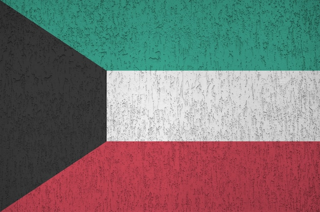 Kuwait flag depicted in bright paint colors on old relief plastering wall. textured banner on rough background