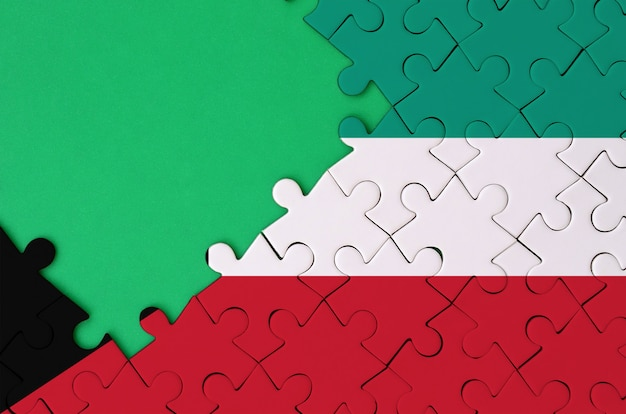 쿠웨이트 국기는 왼쪽에 무료 녹색 복사 공간이있는 완성 된 직소 퍼즐에 그려져 있습니다.