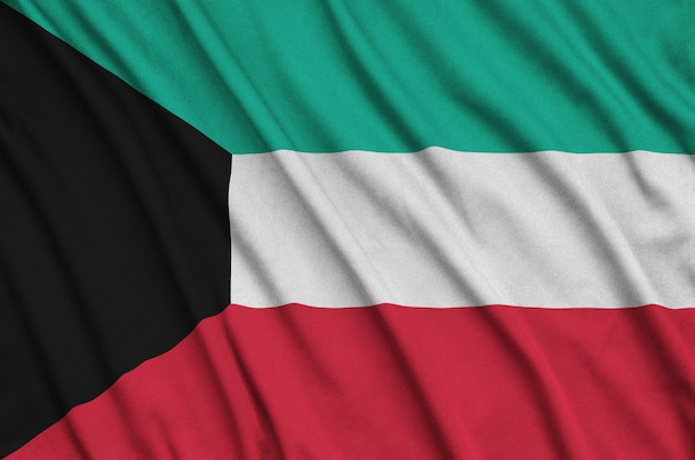 Kuwait flag is depicted on a sports cloth fabric with many folds.
