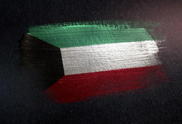 Kuwait flag made of metallic brush paint on grunge dark wall
