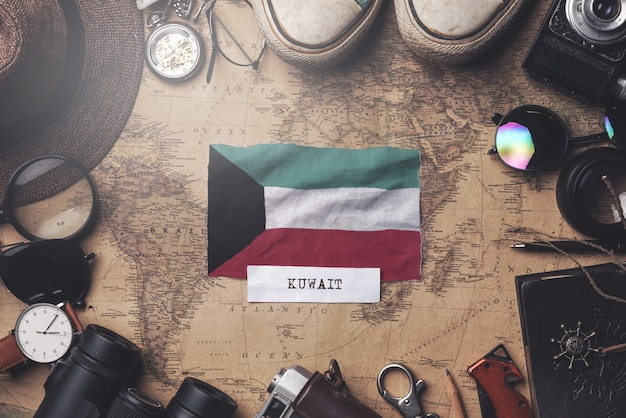 Kuwait flag between traveler's accessories on old vintage map. overhead shot