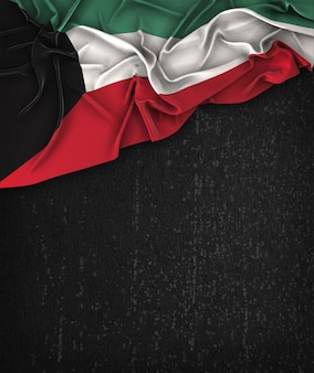 Kuwait flag vintage on a grunge black chalkboard with space for text