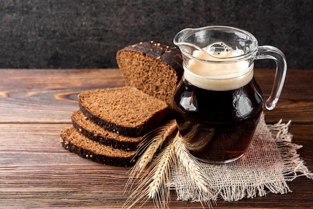 Квас с ржаным хлебом на деревянных фоне