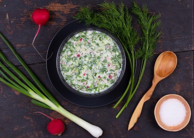 ロシアの夏冷たいスープオクローシカ、野菜、kvass、黒の木製テーブルの上のケフィア