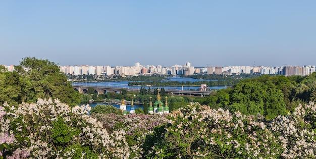 キエフの風景。ウクライナ、キエフ市の植物園にピンクと白のライラックが咲くヴィドゥビチ修道院とドニエプル川の春の景色