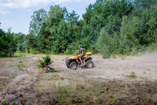 Kyiv- september 2019 man riding a yellow quad atv all terrain vehicle on a sandy forest. extreme sport motion, adventure, tourist attraction.