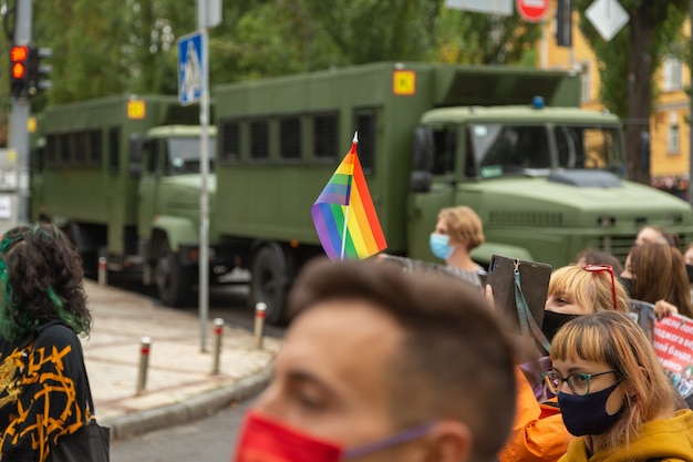 Kyiv, ukraine - 09.19.2021: lgbtq community at the pride parade. participants of the march with rainbow symbols against the background of special police cars.
