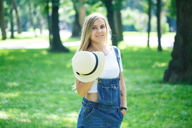 キエフ、ウクライナ-2019年8月デニムのオーバーオールと公園を歩いている軽い帽子の若い美しい女の子