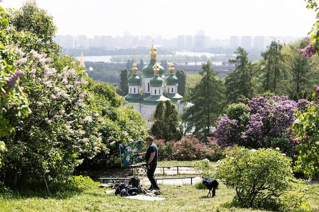 우크라이나 키예프 - 2019년 5월 10일: 키예프의 흐리시코 국립 식물원에 있는 비두비치 수도원, 드니프로 강, 라일락 꽃의 전망. 작가는 꽃이 만발한 나무를 그립니다.