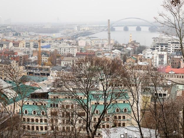 キエフ、ウクライナ-2019年11月16日:霧の日にキエフ市のpodol地区の街並み。 kontraktovaスクエアと観覧車