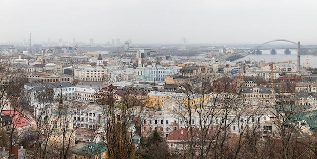 キエフ、ウクライナ-2019年11月16日:霧の日にキエフ市のpodol地区の街並み。コントラクトヴァ広場、観覧車、ポドルスキー橋