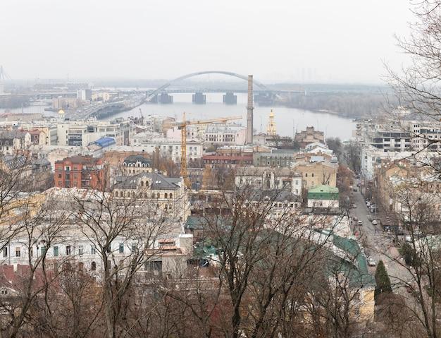 キエフ、ウクライナ-2019年11月16日:霧の日にキエフ市のpodol地区の街並み。ポドルスキー橋
