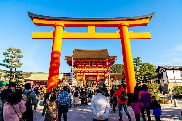 Киото, япония - 11 января 2020 г .: красные ворота тории в фусими инари тайся с туристами и японскими студентами. фусими инари - важнейшее синтоистское святилище.