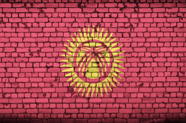 Kyrgyzstan flag is painted onto an old brick wall