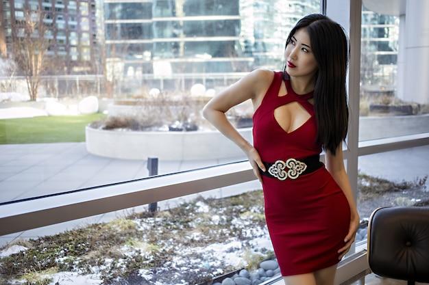 L 여성 아시아 모델 얼굴. 고급 콘도에서 세련된 빨간 립스틱과 드레스를 입고