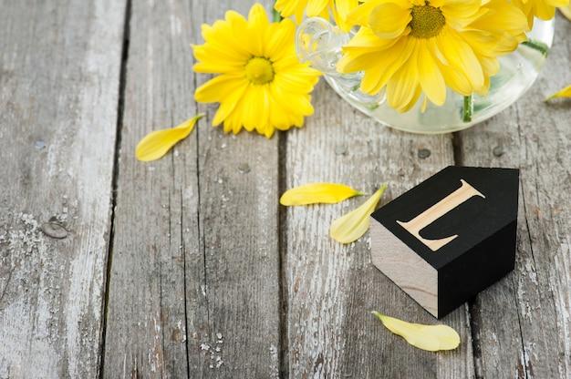 新鮮な黄色のデイジーの花、手紙l