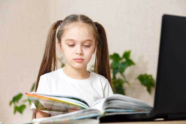 かわいいl女の子はテーブルで宿題をします。
