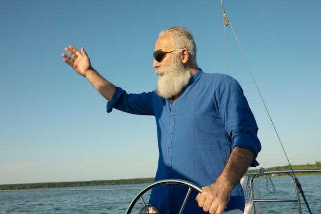 成熟したひげを生やした男が湖でヨットの舵を握って立って、ステアリング、笑顔します。 l