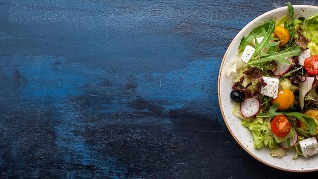 皿に野菜サラダチーズの平面図です。健康とダイエットのコンセプト。 l