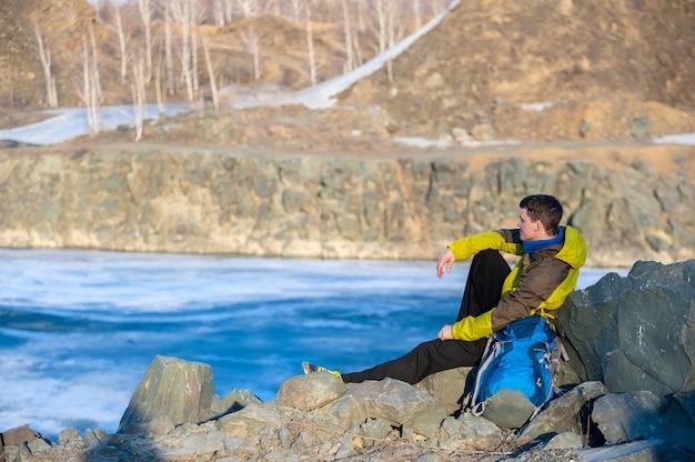 秋lの海岸に座っているバックパックを持つ若者