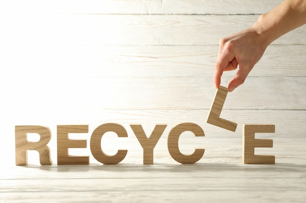 手がリサイクル単語、テキスト用のスペースと木製の背景にlを保持します。