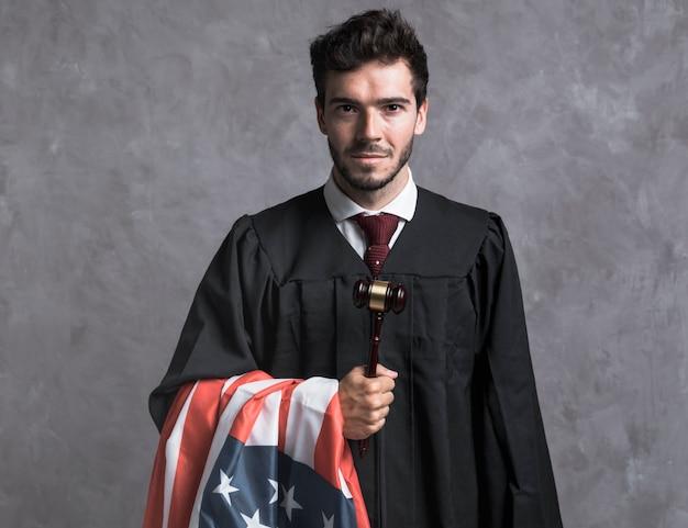 アメリカの国旗と小lを持つフロントビュー裁判官