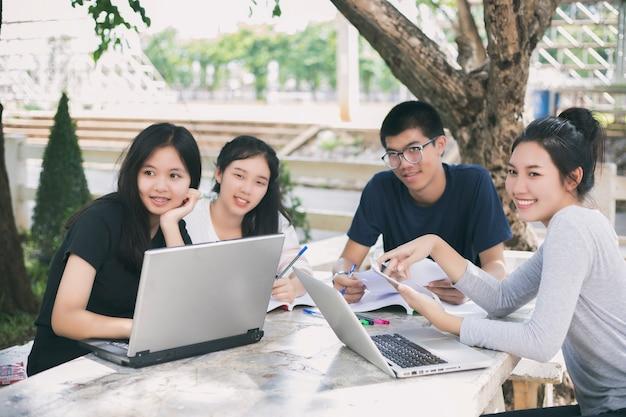 Азиатская группа студентов, использующих планшет и ноутбук с идеями для работы в кампусе l