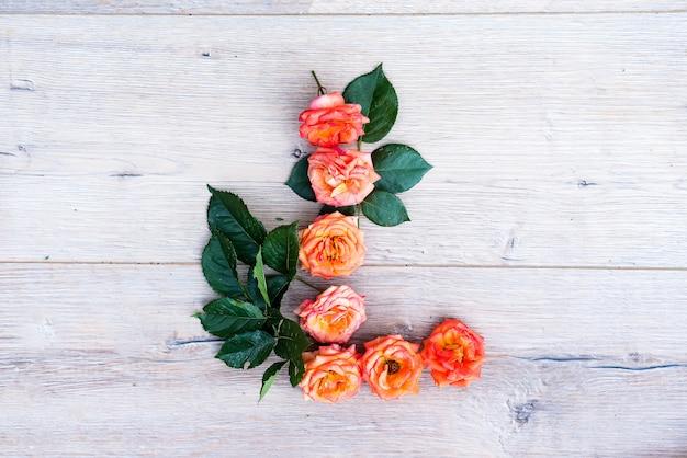 L、バラ花のアルファベットは、灰色の木製の背景に、平らな寝かせ