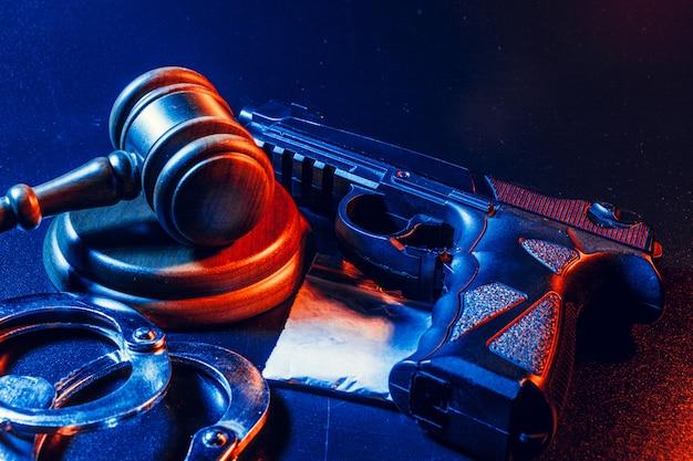 裁判官の小l、暗いテーブルの上に白い粉の袋と手錠。犯罪、強盗、麻薬密売のコンセプト