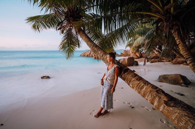 ラディーグ、セイシェル。熱帯の美しい砂浜の金色の夕日の光の中でココヤシの木の近くの女性。