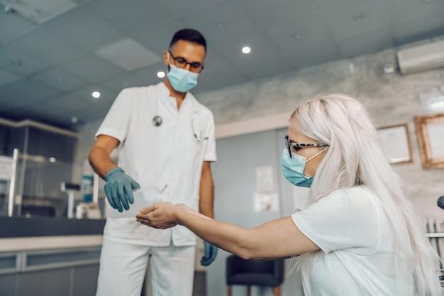 Лаборант держит спирт и наливает его в руки женщины для дезинфекции