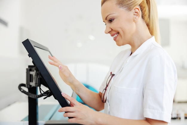 実験室に立ってコンピューターを使用して研究結果を入力するコートの実験助手。