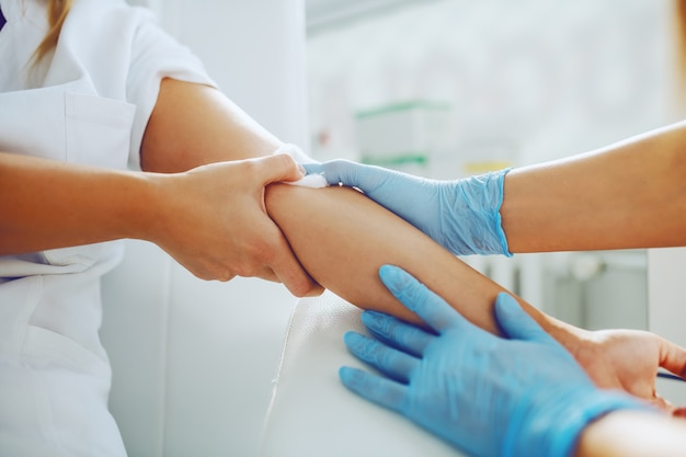 Lab assistant putting absorbent cotton on patient arm after taking blood sample.