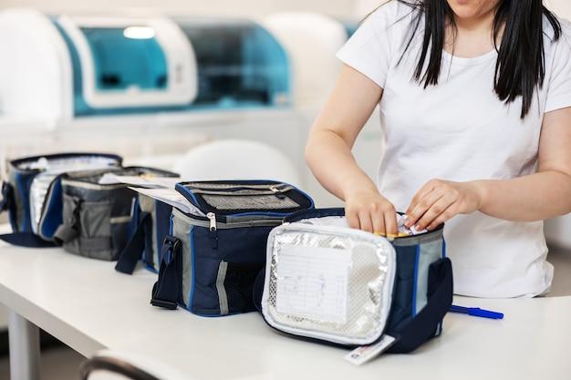 実験室に立っている間にバッグに試験管を入れる実験室の助手。