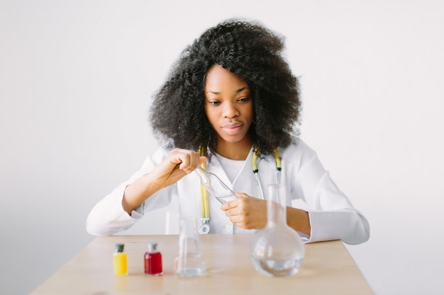 ラボのアシスタントが水質をテストしています。化学実験室で研究を行っている美しい少女研究者化学学生の肖像画