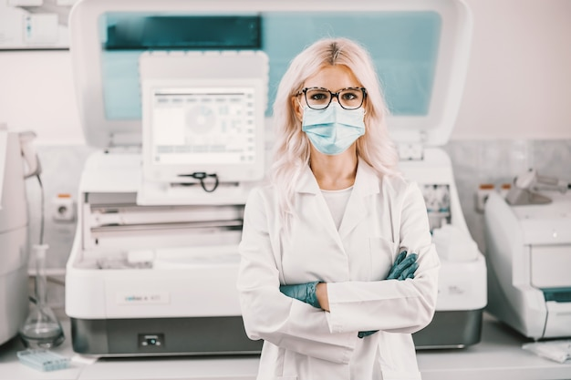 Lab assistant with face mask and rubber gloves standing in laboratory with arms crossed.