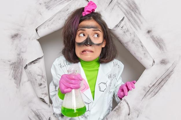 실험실 화학자는 실행 가능한 제품을 생산하기 위해 다양한 물질을 실험하고 녹색 버블링 액체가 있는 유리 제품을 들고 흰색 코트를 입고 분자 수준에서 물질을 검사합니다.