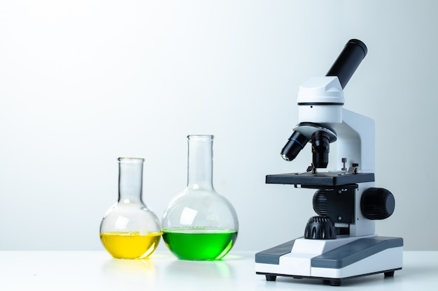 Lab microscope with laboratory glassware on desk