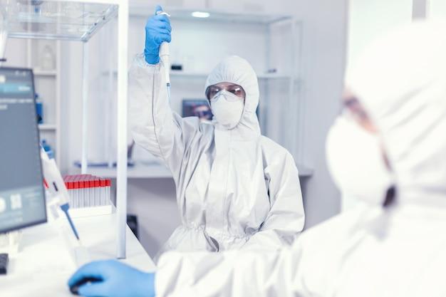 Ученый в лаборатории здравоохранения держит микропипетку с образцом, одетый в костюм ppe против коронавируса. команда микробиологов в исследовательской лаборатории проводит эксперимент во время глобальной пандемии wi